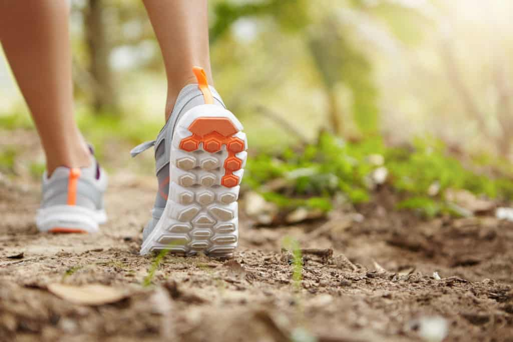 Sports, fitness, nature and healthy lifestyle concept. Young female runner wearing sneakers or running shoes while hiking or jogging in park on sunny day. Woman wearing trail running shoes for hiking