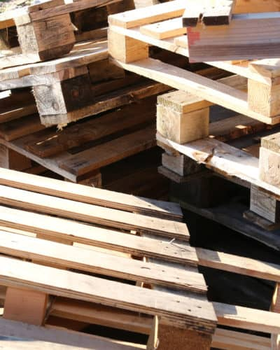 great pile of wooden pallets piled in a landfill waiting for a pallet destroyer to make them into craft projects