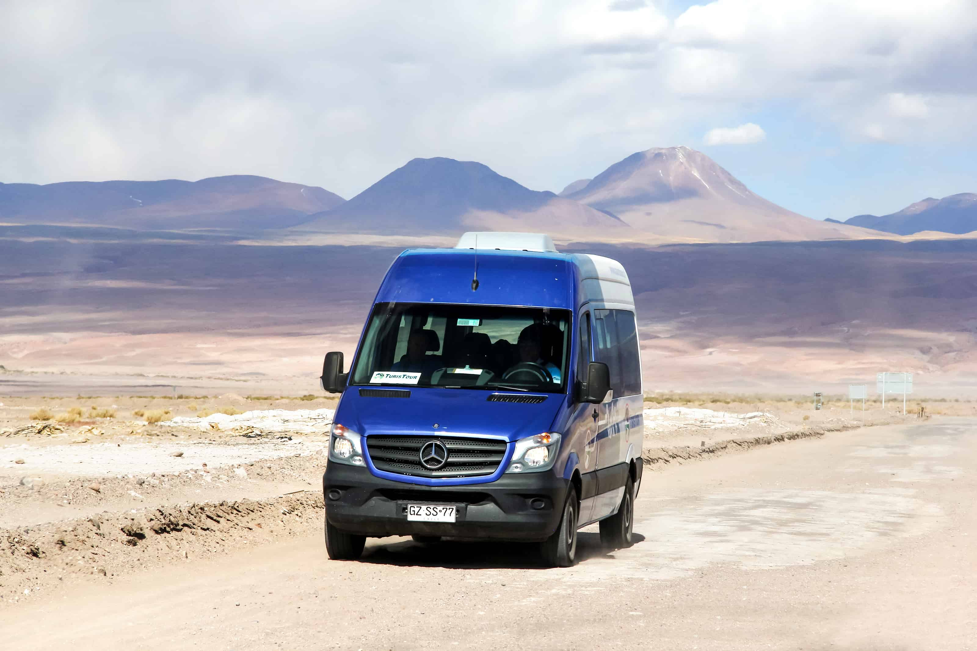 Touristic van Mercedes-Benz Sprinter at the intercity gravel road through the Atacama desert.