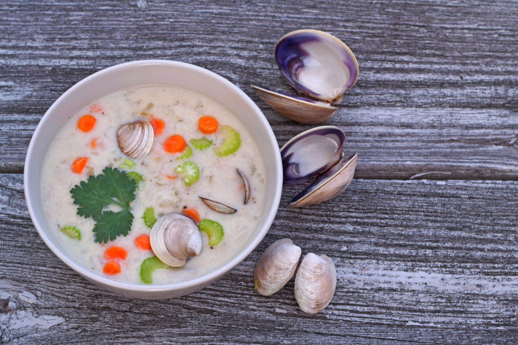 Bowl of clam chowder soup on reclaimed wood background