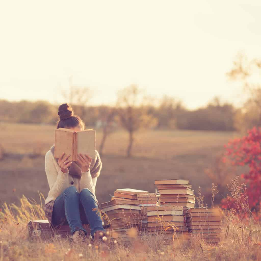 Girl with books in a field