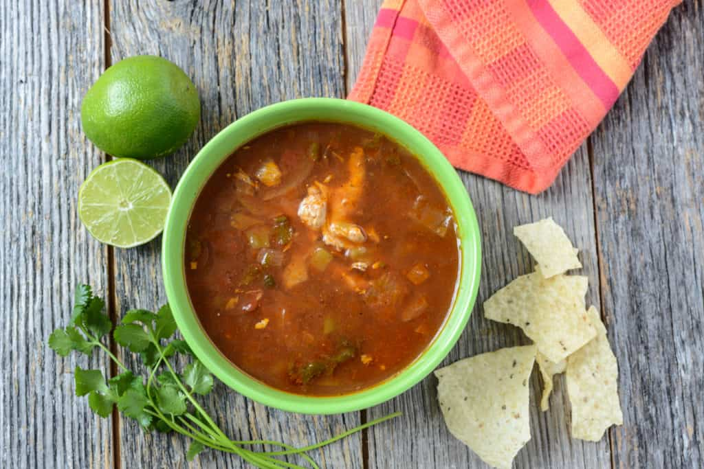 Tortilla Soup with Chips and fresh lime on Rustic Wood