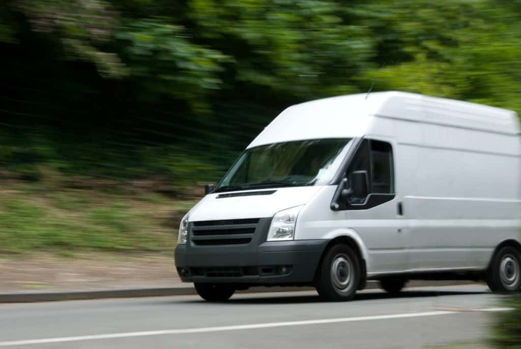 White sprinter van with motion blur on street with green / trees in background