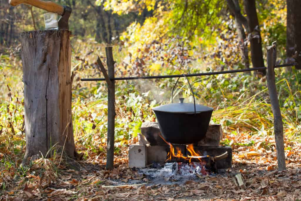 Black Pot over fire and sticks in the woods preparing soup