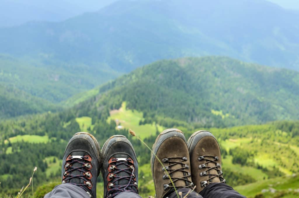 Hiking boots of traveler sitting on high mountain top in travel. Freedom concept