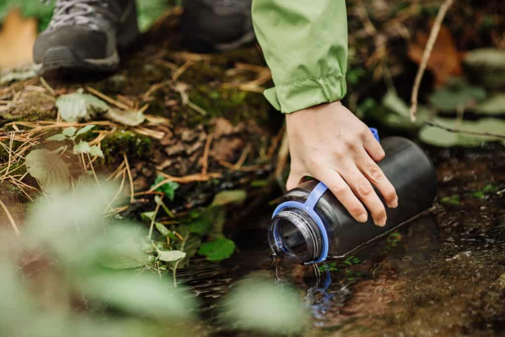 beautiful woman taking water from forest spring on hiking trip
