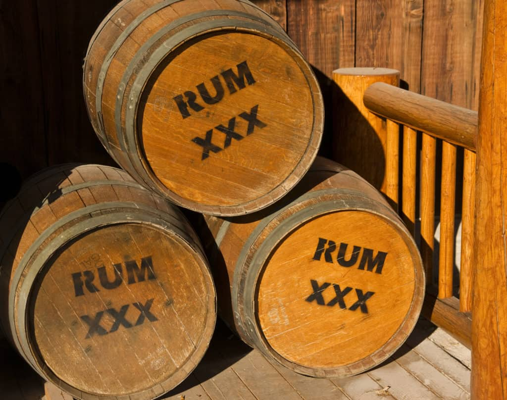 Three wooden casks of rum at dockside