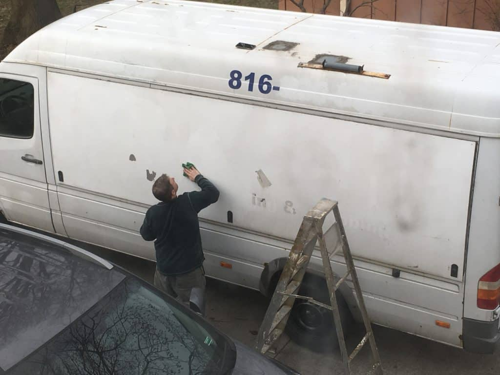 Man working on removing the vinyl lettering from a Sprinter Van