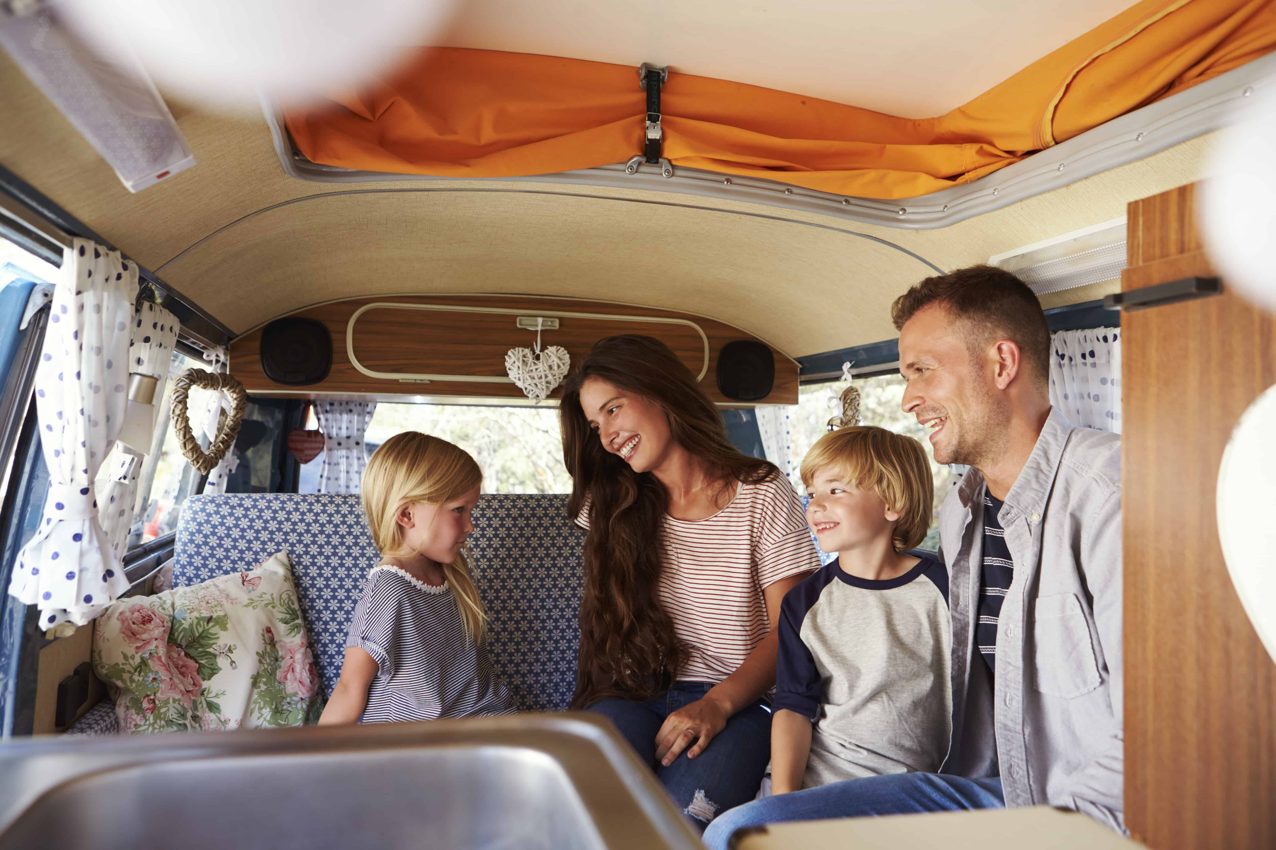 Family sitting inside a camper van looking at each other