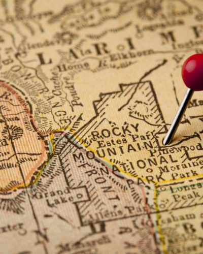 Plan a National Park Family Adventure Rocky Mountain National Park on vintage 1920s map of Colorado with a red pushpin on east entry at Estes Park, selective focus